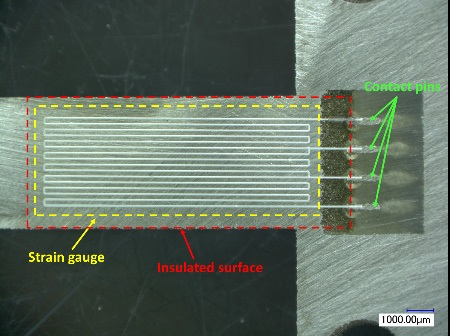 Printed strain gauge and insulation by Aerosol jet printing on a 300 µm-thick flexure element.