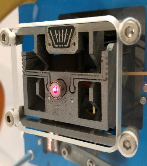 3D printed XY-stage with embedded sensor and external actuator. A laser pointer is integrated to the moving platform to illustrate the capacity of the demonstrator to power a device through flexure blades.
